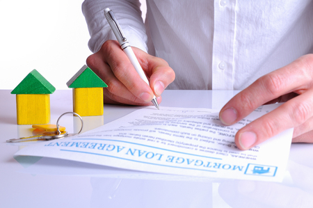 borrowed: client signing the mortgage loan agreement for the purchase of a new home with small wooden houses rear view