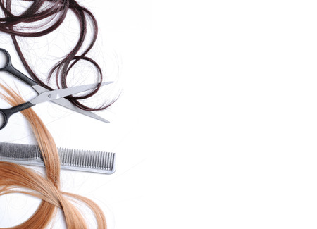 Scissors and comb with brown and blond hair to the left of the image with space to write text, isolated white, top view Imagens