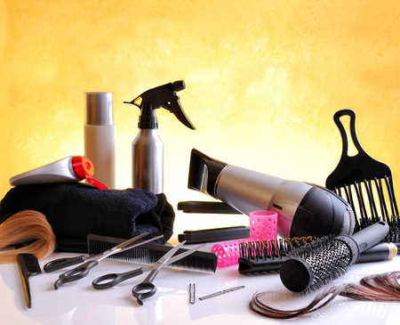 Set hairdressing articles exposed on a glass table and yellow background, horizontal composition