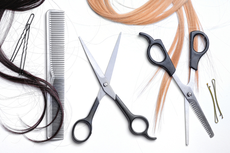tines: two open scissors and comb barber gray lined with tufts of black hair and blond hair with white isolated background top view