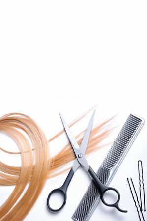 space for writing: Barber scissors and comb with lock of blonde hair isolated with space for writing Stock Photo