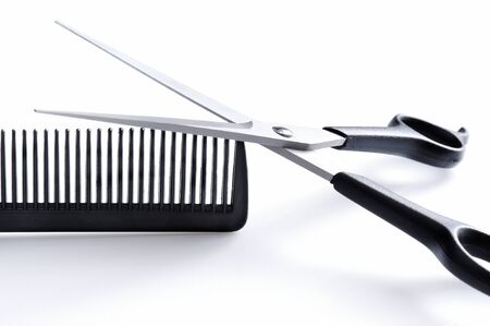 Barber scissors and comb closeup on a white table, isolated on white front view