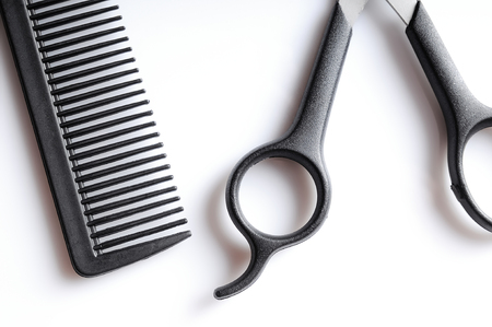 Barber scissors and comb closeup on a white table, isolated on white top view Stock Photo