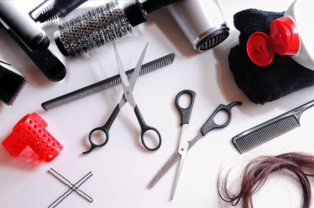 salon background: Horizontal composition hairdressing tools on a white table and white background isolated top view