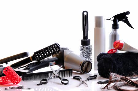 secador de pelo: Composición horizontal peluquería herramientas sobre una mesa blanca y fondo blanco aislado Foto de archivo
