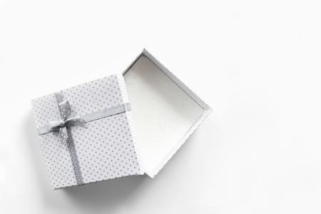 cajas de carton: Blanco caja de regalo vacío con pequeños círculos de color gris cinta de tela con corbata gris. Vista superior blanco aislado Foto de archivo