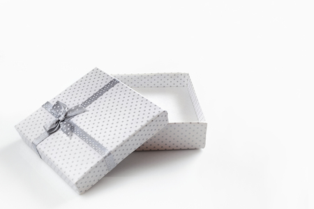 gift box: White empty gift box with small circles gray fabric tape with gray tie. isolated white front view Stock Photo