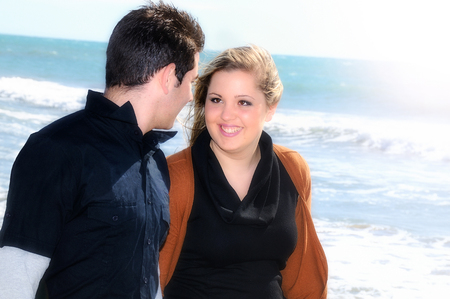 affectionate action: young couple in love black and brown dresses smiling walking along the seashore