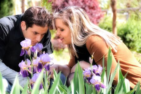 Young couple in love squatting smelling a purple lilies in a park Stock Photo