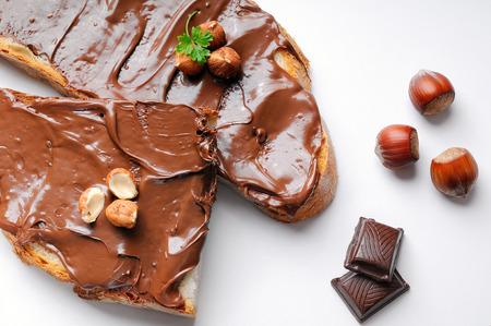 チョコレート クリームとヘーゼル ナッツのパンの 2 つのスライスは白い分離の平面図です。ヘーゼル ナッツとチョコレートのデコレーション。 写真素材