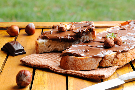 Two slices of bread with chocolate cream and hazelnuts on a wooden table outdoors. Hazelnut knife and chocolate decoration.