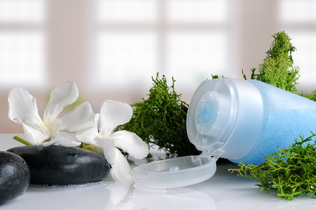 Blue exfoliating gel with seaweed on a white glass table in a bath Foto de archivo