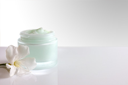 pureness: Glass open jar with facial or body cream on white table. with flower and white isolated background. Front view.