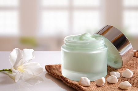 facial cream: Glass open jar with facial or body cream on burlap. with lid, stones and flower. Background windows. Front view.