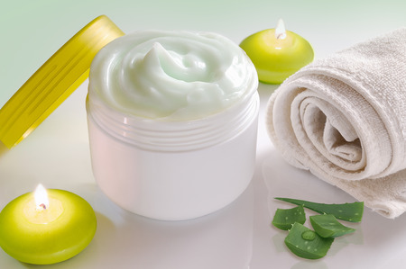 White plastic container with facial or body cream of aloe vera. Candles, towel and plant decoration and green background isolated. Top view