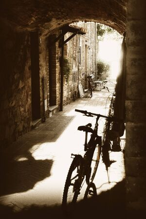 ancient cobbled passageway with stone houses and bicycle supported on the facades backlit
