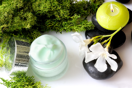 Open cream jar algae. Flowers, black stones and seaweed decoration. Top view Stock Photo
