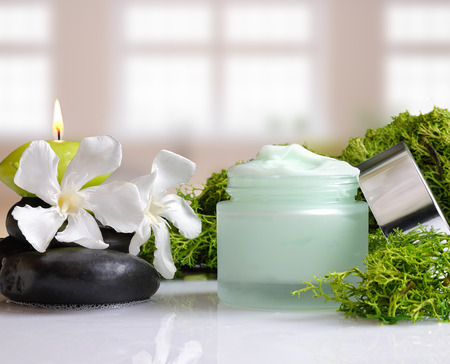 Open cream jar algae. Flowers, black stones and seaweed decoration. Windows background. Front view
