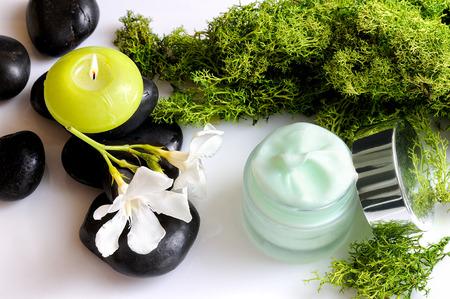 Open cream jar algae. Flowers, black stones and seaweed decoration. Top view Foto de archivo