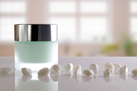 pureness: Glass closed jar with facial or body cream on white table with small white stones. Front view. Windows background. Stock Photo