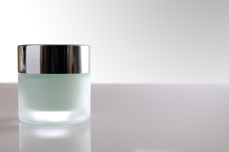 Glass closed jar with facial or body cream on white table. Front view. White isolated background