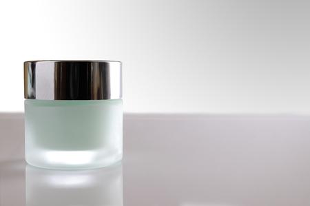 limpieza de cutis: Vidrio cerrado frasco con crema facial o corporal en el cuadro blanco. Vista frontal. Fondo blanco aislado