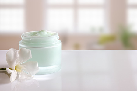 Glass open jar with facial or body cream on white table. with flower and background windows. Front view.