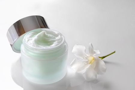 crinkles: Glass open jar with facial or body cream on white table with flower. Top view. White isolated.