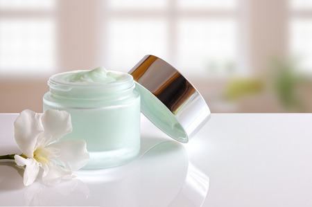 Glass open jar with facial or body cream on white table. with lid and flower. Background windows. Front view.