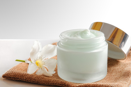 Glass open jar with facial or body cream on burlap. With lid and flower.Isolated background. Front view.