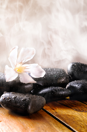 sauna: Group of black stones on wood base, steam background. Sauna, therapy, relaxation, and health concept.Vertical composition.