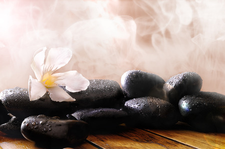 sauna: Group of black stones on wood base, steam background. Sauna, therapy, relaxation, and health concept. Stock Photo
