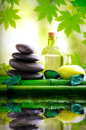 essences: Stones and massage oil over bamboo reflected in water in nature. With background of green leaves and bokeh. Alternative treatments of natural essences for body care and relaxation. Square composition. essences Stock Photo