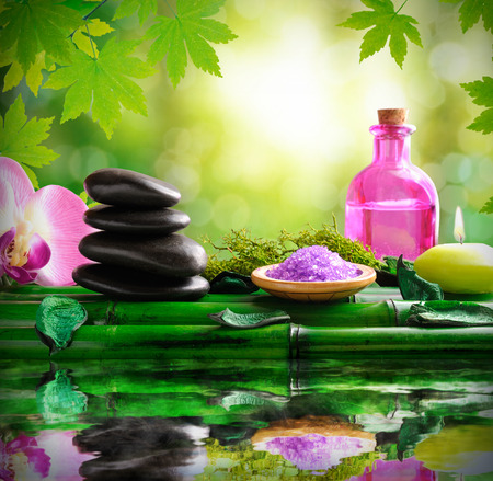 essences: Stones, oil, bath salts and massage over bamboo reflected in water in nature. With background of green leaves and bokeh. Alternative treatments of natural essences for body care and relaxation. Square composition. Stock Photo