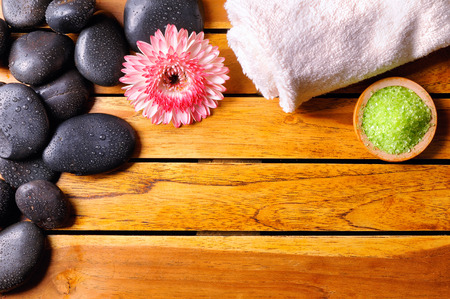essences: Black stones with water drops in the top left corner, flower, towel and bath salts on wooden slats. Sauna and massage concept. Horizontal composition. Top view