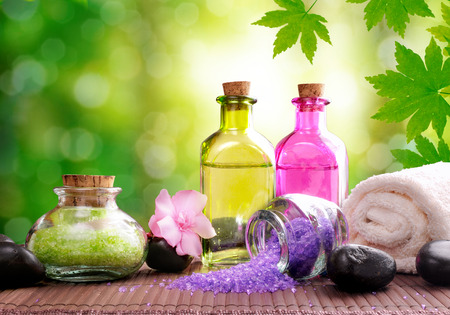 essences: Bath salts and body oil on wood mat. Nature leaves and bokeh background. Horizontal composition Stock Photo