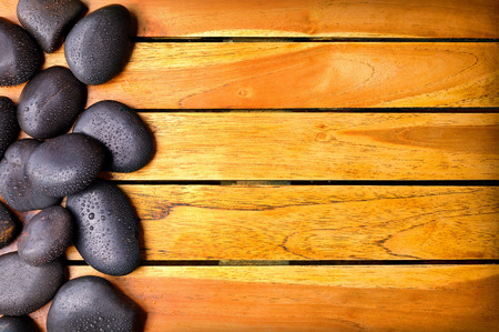 sauna: Black stones with water drops on the left side on wooden slats. Sauna and massage concept. Horizontal composition. Top view