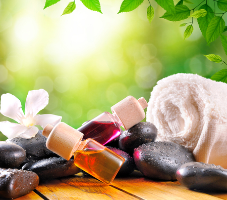 essences: Oil and essences for body care and towel with black stones on wood base. Green leaves and bokeh background. Square composition. Stock Photo