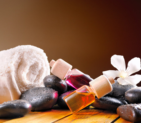 essences: Containers and oil balls and essences for body care. With black stones, towel and sheets on wooden base. Brown gradient background. Square composition