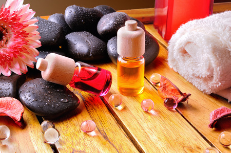 essences: Containers and oil balls and essences for body care. With black stones, towel and sheets on wooden base. Brown gradient background. Stock Photo