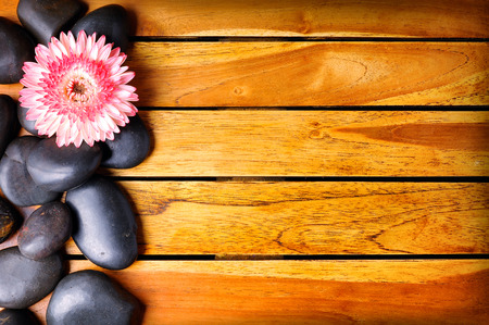essences: Black stones and flower on the left side on wooden slats. Sauna and massage concept. Horizontal composition. Top view Stock Photo