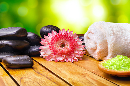 essences: Salt and essences for body care bath. With black stones, towel and flower on wood base. Green bokeh background. horizontal composition