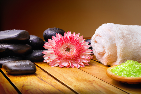 stones with flower: Black stones, flower, towel and bath salts on wooden slats. Brown gradient background. Horizontal composition