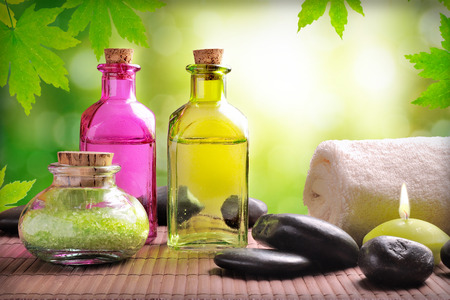 essences: Bath salts and body oil on wood. Nature leaves and bokeh background. Horizontal composition Stock Photo