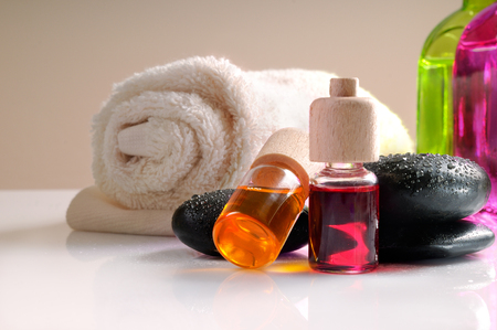 essences: Oils stones and towel on glass table for massage. Brown gradient background. Horizontal composition. Front view