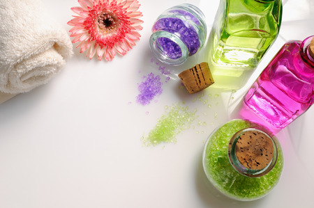 essences: Oils and bath salts on white glass table. Decorated with flower and towel. Horizontal composition. Top view Stock Photo