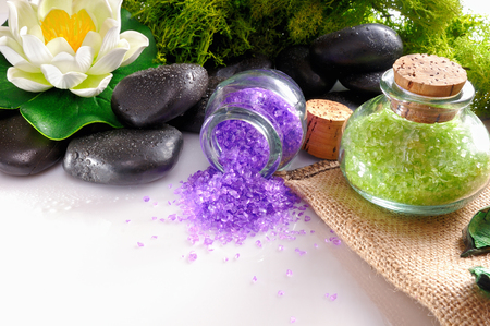 essences: Bath salts close up with black stones and moss flower glass on white table. Horizontal composition