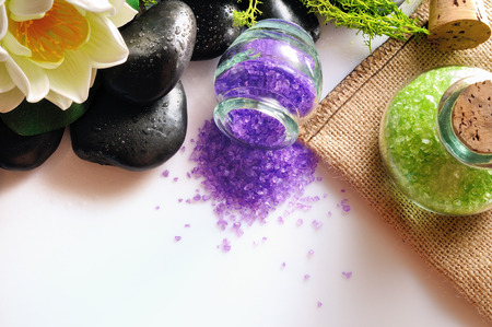 essences: Bath salts close up with black stones and moss flower glass on white table. Horizontal composition. Top view Stock Photo