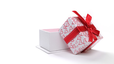 open box: Decorative open white gift box with red ribbon and painted hearts. Front view. White isolated background
