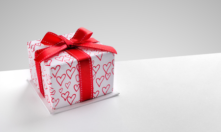 Decorative gift box with red ribbon and hearts printed on white table. Top view left. Grey background. Horizontal composition.